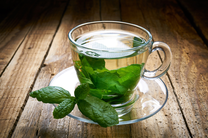 Tea with mint leaves on old wooden boards